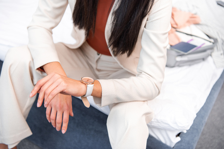 cropped shot of elegant young woman in stylish white suit sitting on bed