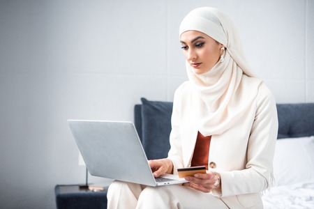 young muslim woman holding credit card and using laptop at home