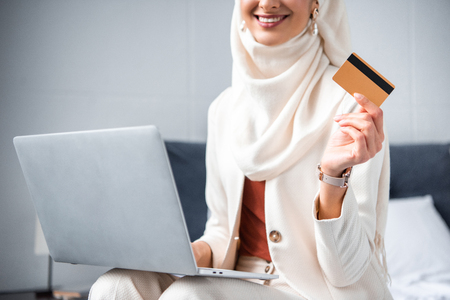 cropped shot of smiling muslim woman holding credit card and using laptop at home 免版税图像 - 116419627