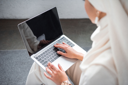 cropped shot of young muslim woman using laptop with blank screen