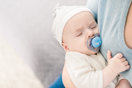 cropped shot of mother holding sleeping son with pacifier in hands