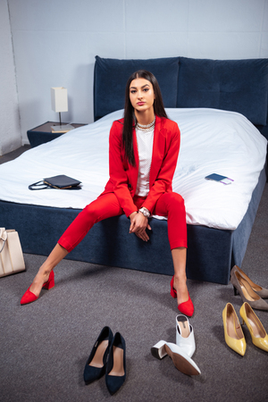 beautiful young woman in stylish red suit sitting on bed and looking at camera, various fashionable shoes on floor