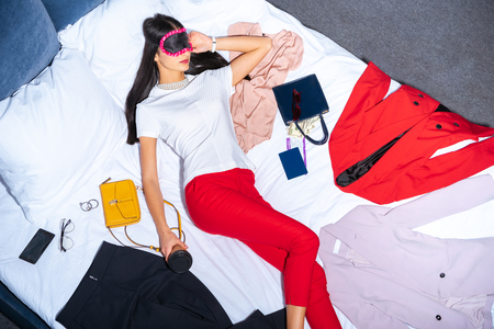 top view of girl in eye mask holding coffee to go and sleeping on bed with clothes, passport and money 版權商用圖片