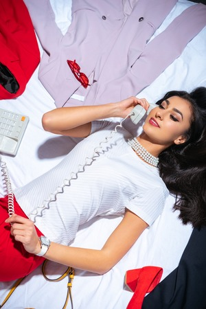high angle view of beautiful smiling young woman lying on bed and talking by telephone