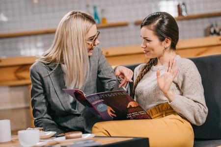 attractive women chatting near beauty magazine Stock fotó