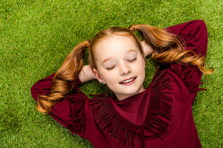 top view of cute schoolgirl lying on lawn with closed eyes Foto de archivo