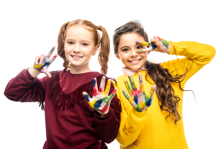 smiling schoolgirls showing peace signs with hands painted in colorful paints and looking at camera isolated on white Imagens