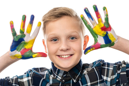 close up view of cute boy looking at camera and showing hands painted in colorful paints isolated on white