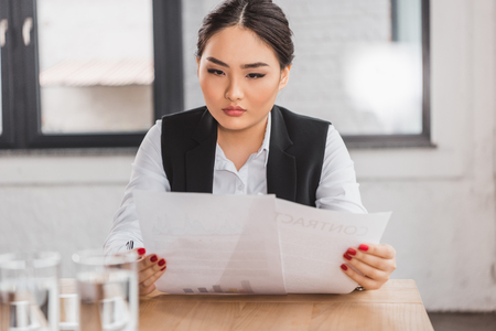 beautiful concentrated kazakh businesswoman working with contract in office Stok Fotoğraf - 116422138
