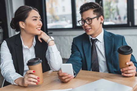young business people with paper cups using smartphone and smiling each other in office Stok Fotoğraf - 116299631