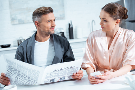 man in robe reading business newspaper while woman using smartphone during breakfast in kitchen