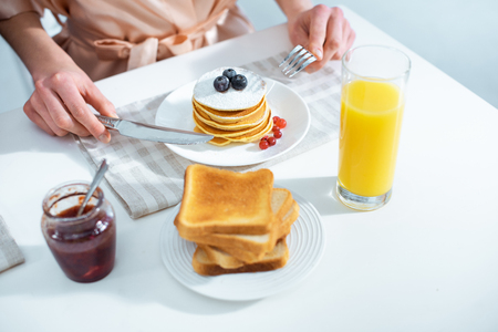 cropped view of woman having breakfast with pancakes and orange juice in kitchen