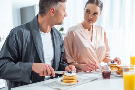 beautiful couple in robes during breakfast with pancakes and orange juice in kitchen Stock Photo