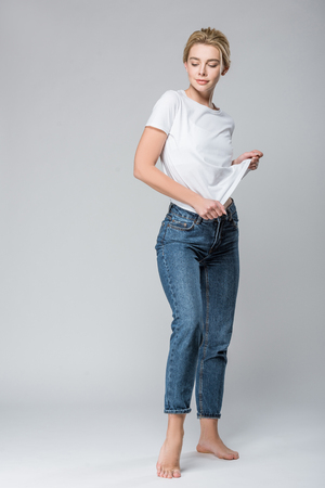 beautiful smiling woman in jeans undressing isolated on grey Stok Fotoğraf