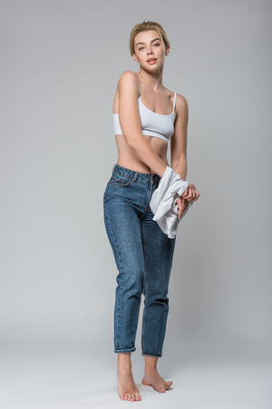 slim blonde girl in jeans and white bra undressing isolated on grey 版權商用圖片