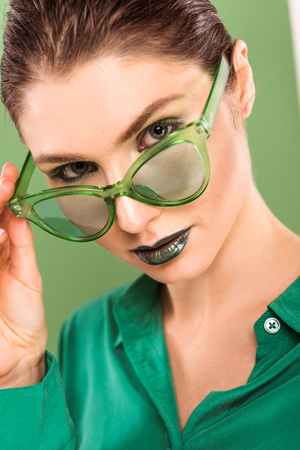 portrait of beautiful fashionable woman in sunglasses looking at camera with sea green on background