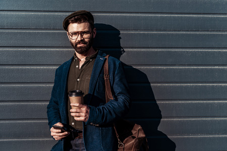 handsome bearded man in glasses and cap holding paper cup and smartphone