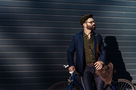 handsome bearded man in glasses and cap holding bicycle