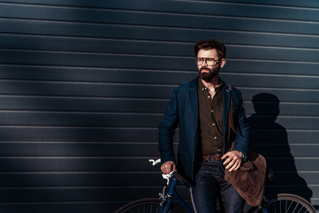 handsome bearded man in glasses and cap holding bag and bicycle Stock Photo