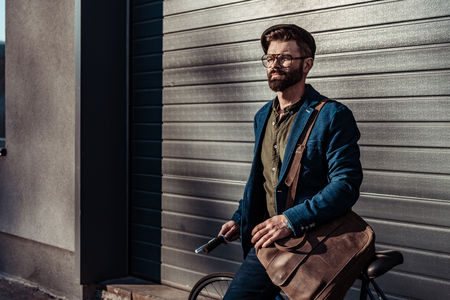 handsome bearded man in glasses and cap holding bicycle and smiling Stock Photo