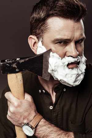 serious handsome man with foam on face shaving beard with ax isolated on brown 스톡 콘텐츠