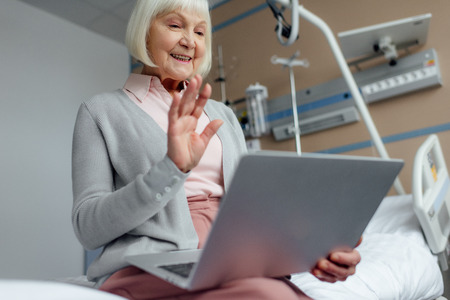 happy senior woman sitting on bed, using laptop and waving with hand while having video call in hospital
