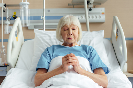 senior woman lying in bed with folded hands and praying in hospital 스톡 콘텐츠