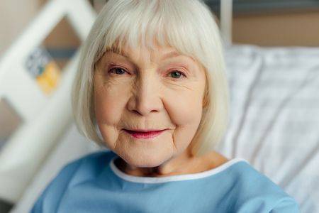 portrait of smiling senior woman with grey hair looking at camera in hospital