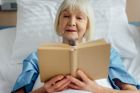 senior woman lying in bed and reading book in hospital 스톡 콘텐츠
