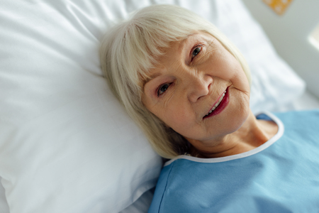 selective focus of smiling senior woman with grey hair lying in bed in hospital 스톡 콘텐츠