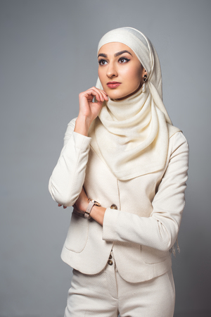 beautiful pensive young muslim woman looking away isolated on grey