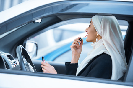 young muslim woman sitting in car and applying makeup Standard-Bild - 116324842