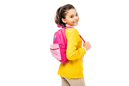 adorable child holding pink backpack and smiling at camera isolated on white