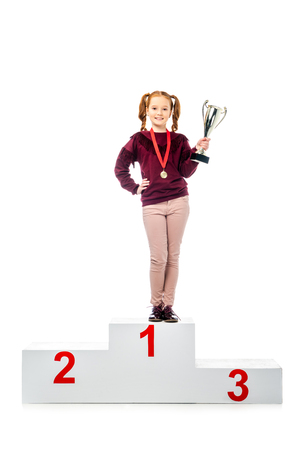 smiling schoolgirl with medal standing on winner podium, holding trophy cup and looking at camera isolated on white Stock Photo