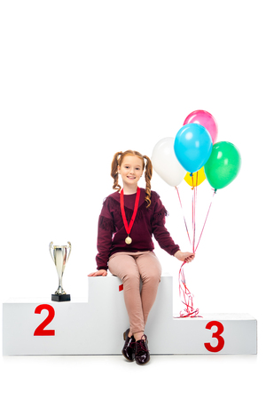 smiling schoolgirl sitting on winner podium near trophy cup, holding colorful balloons and looking at camera isolated on white Imagens