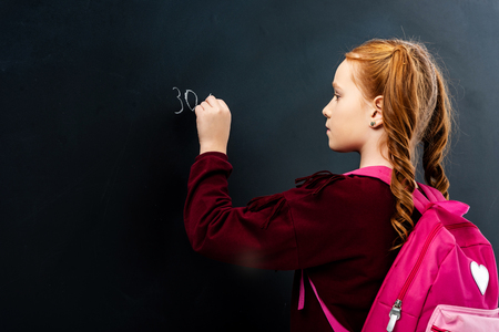 schoolgirl with pink backpack writing on blackboard with chalk