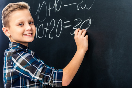 smiling boy writing math example on blackboard with chalk and looking at camera