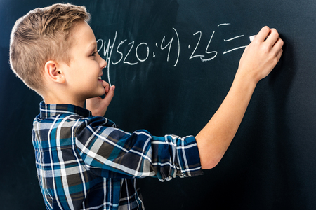 smiling boy writing math example on blackboard with chalk Stock fotó - 116324380
