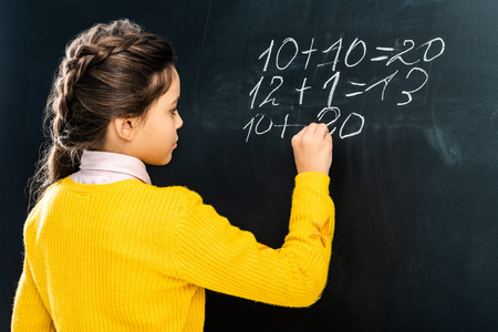 schoolgirl in yellow sweater writing on blackboard with chalk Фото со стока