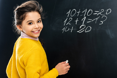 cheerful schoolgirl in yellow holding chalk and looking at camera in front of blackboard Reklamní fotografie