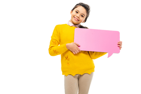 cheerful schoolgirl holding pink speech bubble and looking at camera isolated on white