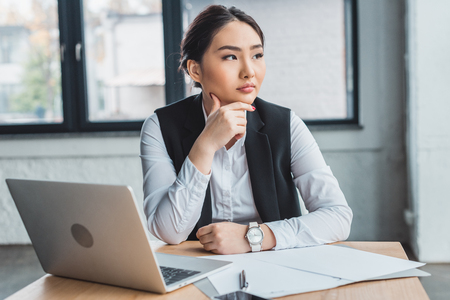 pensive young kazakh businesswoman sitting at workplace and looking away in office