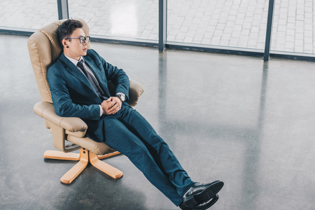 high angle view of young businessman in suit sitting in chair at workplace