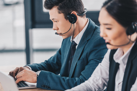 young kazakh coworkers in headsets working together in call center Stok Fotoğraf