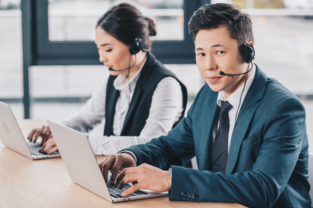 young man in headset looking at camera while working with female colleague in call center Stok Fotoğraf - 116324551