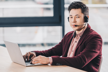 handsome young kazakh businessman in headset using laptop and looking at camera in office