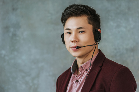handsome young asian call center operator looking at camera on grey