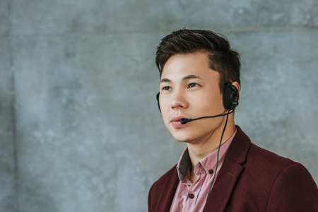 handsome young asian call center operator looking away on grey