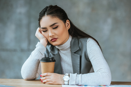 tired young businesswoman holding coffee to go and sitting with closed eyes at workplace Stok Fotoğraf - 116324422