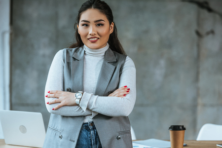 beautiful kazakh businesswoman standing with crossed arms and smiling at camera in office